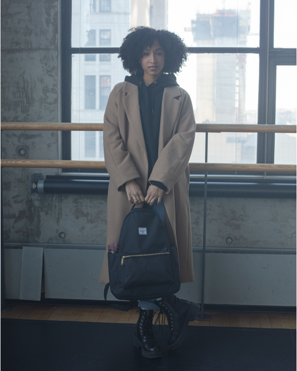 A woman in a ballet studio holding a Nova Backpack