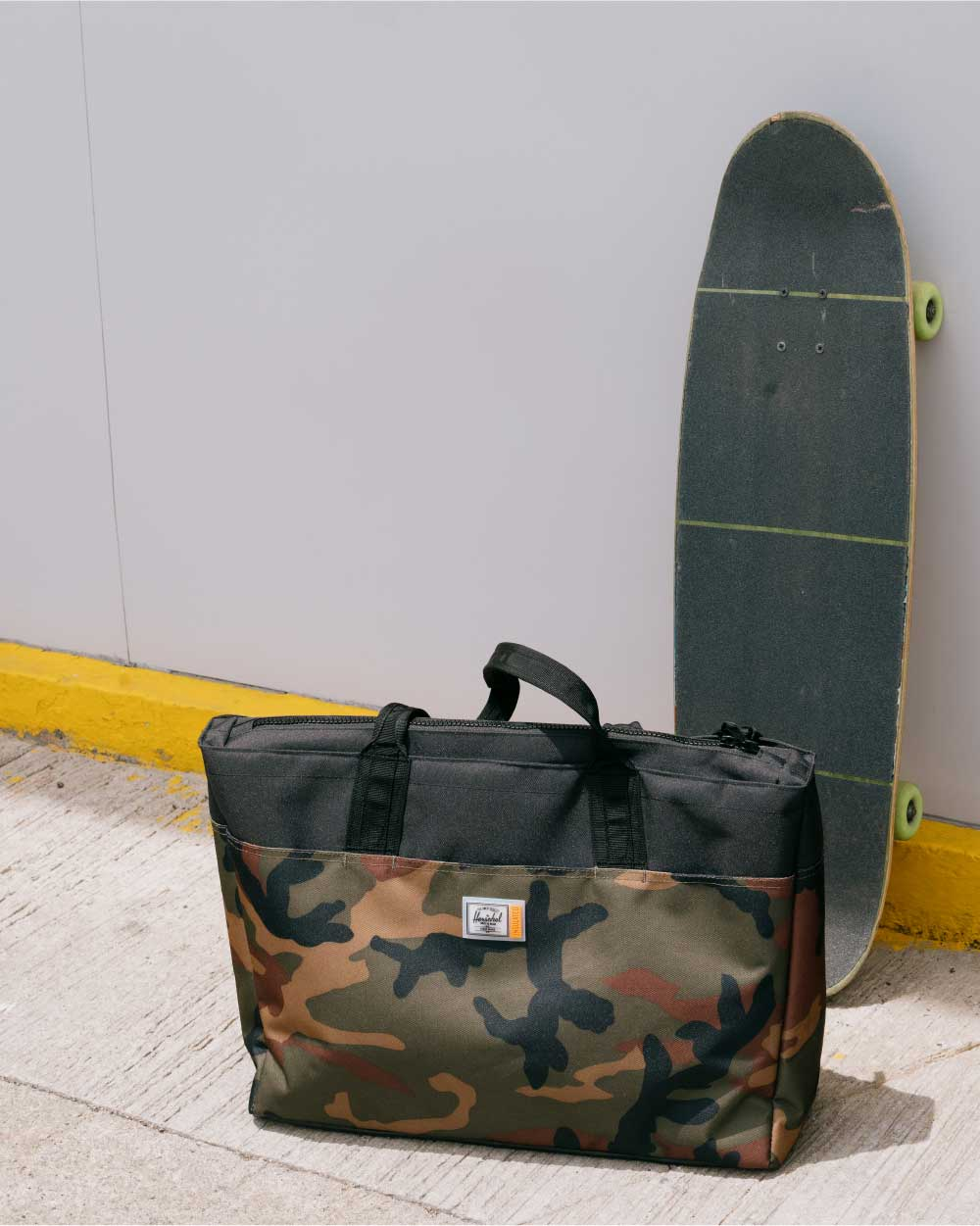 a black/camo insulated alexander zip tote sits in front of a skateboarde leaning against a wall