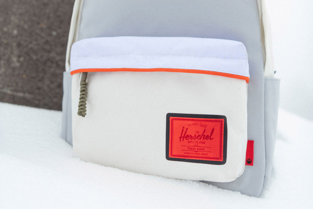 classic xl backpack with a bright red classic woven label sits on a snowy surface