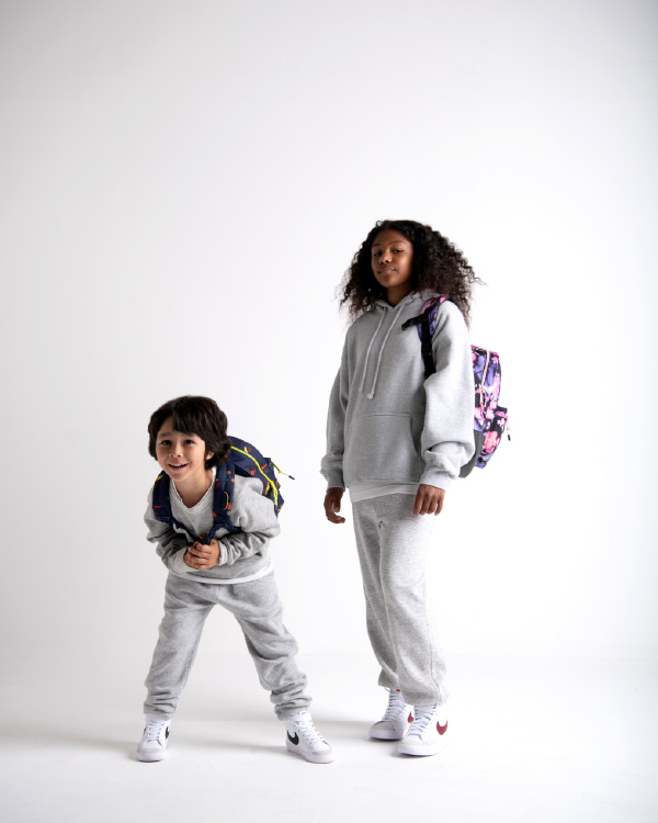 A couple of children wearing their Little Herschel backpacks against a grey background